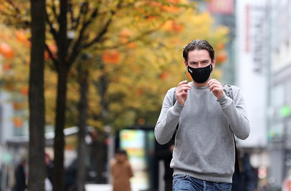 A person wearing a face mask walks down Market street in Manchester. Stringent Tier 3 coronavirus restrictions have been imposed on the Greater Manchester area after negotiations between ministers and local leaders broke down after more than a week. (Photo by Martin Rickett/PA Images via Getty Images)