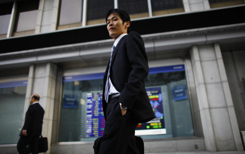A man walks by a securities company in Tokyo Thursday, Nov. 22, 2012. World stock markets rose Thursday after a survey showed that China's manufacturing expanded for the first time in 13 months, rare good news for the struggling global economy. Japan's Nikkei 225 index jumped 1.6 percent to close at 9,366.80 - its highest finish since May 2 - as a recently weakened yen provided a vital boost to the export-heavy index. (AP Photo/Junji Kurokawa)