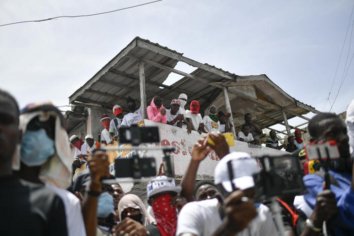 """Members of the gang led by Jimmy Cherizier, alias Barbecue, a former police officer who heads a gang coalition known as """"G9 Family and Allies,"""" watch a march to demand justice for slain Haitian President Jovenel Moise in La Saline neighborhood of Port-au-Prince, Haiti, Monday, July 26, 2021. Moise was assassinated on July 7 at his home. (AP Photo/Matias Delacroix)"""