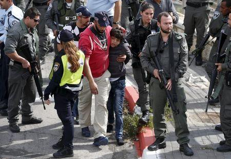 Israeli police lead away a Palestinian minor (C) they said stabbed an Israeli security guard in Pisgat Zeev, which lies on occupied land that Israel annexed to Jerusalem after the 1967 Middle East war, November 10, 2015. REUTERS/Ammar Awad