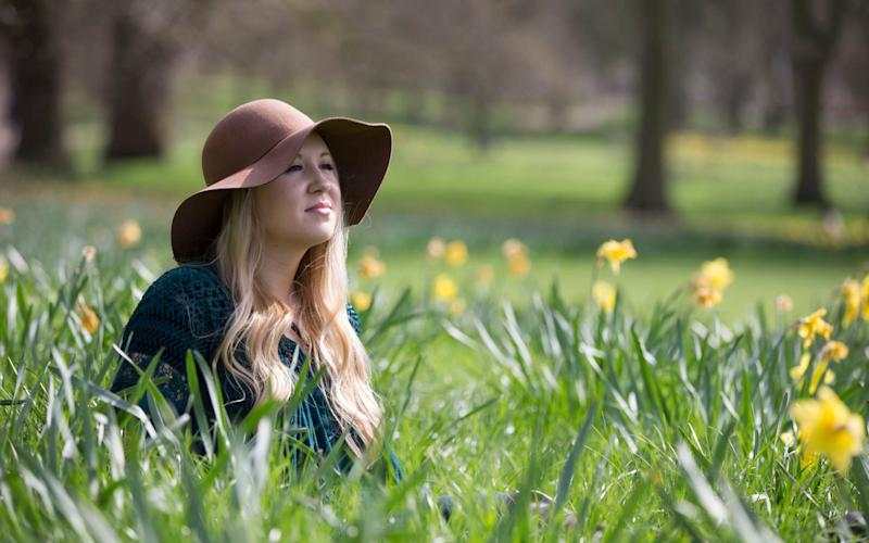 American tourist Lauren, on holiday from Pennsylvania, enjoys the unseasonably warm weather in Green Park, central London - Copyright ©Heathcliff O'Malley , All Rights Reserved, not to be published in any format without p