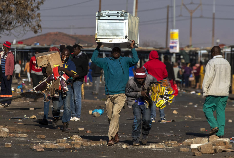 People carry items at Letsoho Shopping Centre in Katlehong, east of Johannesburg, South Africa, Monday, July 12, 2021. Police say six people are dead and more than 200 have been arrested amid escalating violence during rioting that broke out following the imprisonment of South Africa's former President Jacob Zuma. (AP Photo/Themba Hadebe)