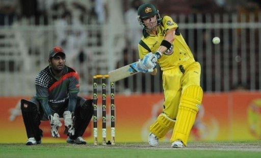 Australian captain Michael Clarke (R) hits a six as Afghanistan's wicketkeeper Mohammad Shehzad looks on