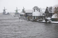 Snow and strong winds pounded houses and windmills along the Zaanse Schans river in Zaandam, Netherlands, Sunday, Feb. 7, 2021. (AP Photo/Peter Dejong)