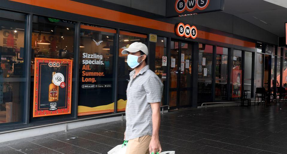 A man with a face mask walks past BWS in Berala.