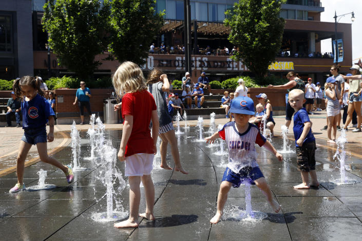 Kids play around a water fountain outside of Chicago's Wrigley Field before a baseball game, Friday, June 11, 2021, as Chicago and rest of Illinois fully reopens ending an over a year-long COVID-19 restrictions. (AP Photo/Shafkat Anowar)
