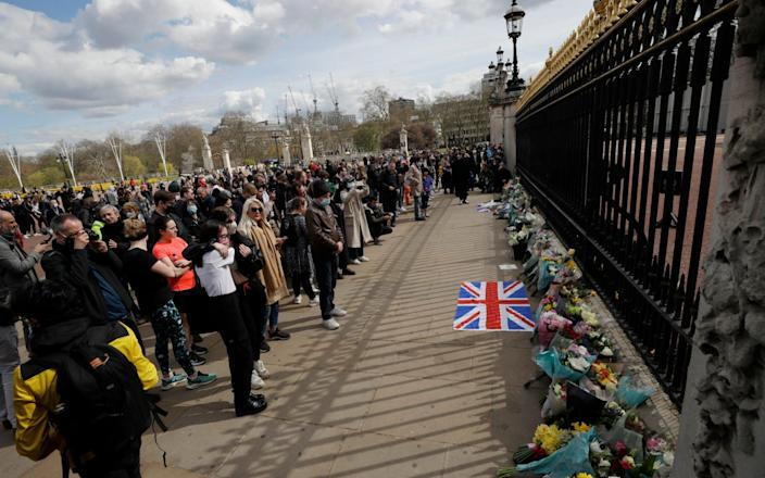 People see flowers left in front of the gates of Buckingham Palace in London-Matt Dunham / AP