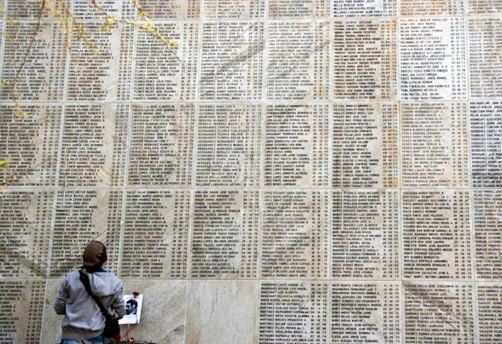 A person stands in front of a wall with the names of people killed during the military dictatorship (1973-1990), in Santiago on September 7, 2014 (AFP Photo/Martin Bernetti)
