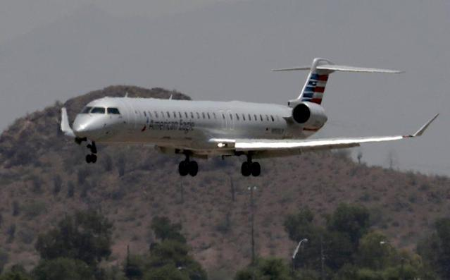 An American Eagle jet is seen through heat ripples as it lands at Sky Harbor International Airport in Phoenix.