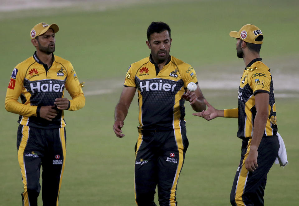 Peshawar Zalmi' Wahab Riaz, center, talks to teammates Shoaib Malik, left, and Saqib Mahmood while he walks toward his bowling point during a Pakistan Super League T20 cricket match between Islamabad United and Peshawar Zalmi at the National Stadium, in Karachi, Pakistan, Saturday, Feb. 27, 2021. (AP Photo/Fareed Khan)