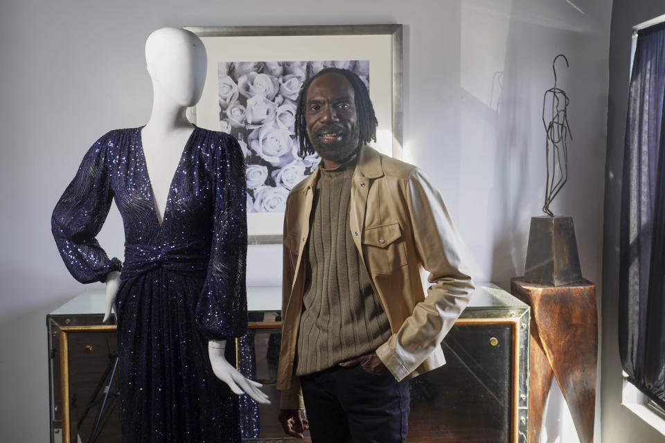 """Fashion designer Kevan Hall pauses for a picture with a Vee Neck Twist Gown, part of his """"Galaxy Collection"""" at his haute couture atelier in West Los Angeles Thursday, March 18, 2021. A year ago, Hall quickly moved away from his trademark gowns and cocktail dresses to caftans, tunics and pull-on pants. Now Hall is adding back some dressier looks, but he's eliminating the full skirts and scaling back the beading in favor of simple gowns and dresses in knit and tulle fabrics. (AP Photo/Damian Dovarganes)"""