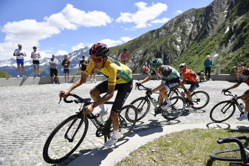 Leader Egan Bernal from Colombia, left, leads the pack over the Gotthard pass during the ninth and final stage, a 101.5 km race with start and finish in Goms, Switzerland, at the 83rd Tour de Suisse UCI ProTour cycling race, on Sunday, June 23, 2019. (Gian Ehrenzeller/Keystone via AP)