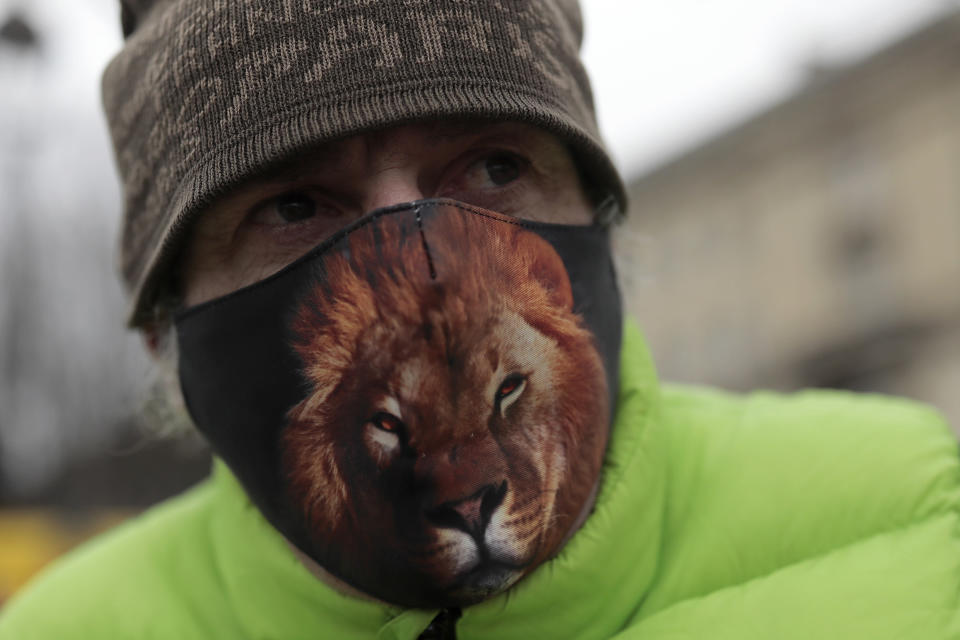 """Frederic Edelstein, an animal trainer for the Pinder Circus, wears a mask printed with a lion during a protest Tuesday, Jan.26, 2021. French lawmakers start debating Tuesday a bill that would ban using wild animals in traveling circuses and keeping dolphins and whales in captivity in marine parks, amid other measures to better protect animal welfare. Circus workers stage a protest outside the National Assembly to denounce what they consider """"a mistake."""" (AP Photo/Lewis Joly)"""