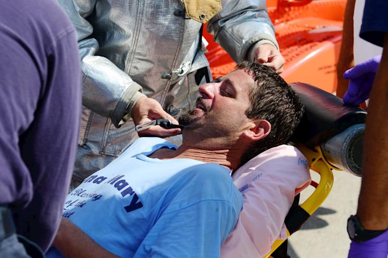 In this photo of Wednesday, July 24, 2013, provided by the US Coast Guard, lobsterman John Aldridge lies on a stretcher at Air Station Cape Cod in Sandwich, Mass. after being rescued by a Coast Guard helicopter. Aldridge, a fisherman for 19 years, fell overboard and spent 12 hours floating in the ocean south of Montauk, N.Y. before he was rescued. He credited his rubber boots for saving his life. Aldridge was not wearing a life jacket when he fell into the ocean and used the boots for floatation until he was found Wednesday afternoon, more than 40 miles from his boat. (AP Photo/US Coast Guard, Ross Ruddell)