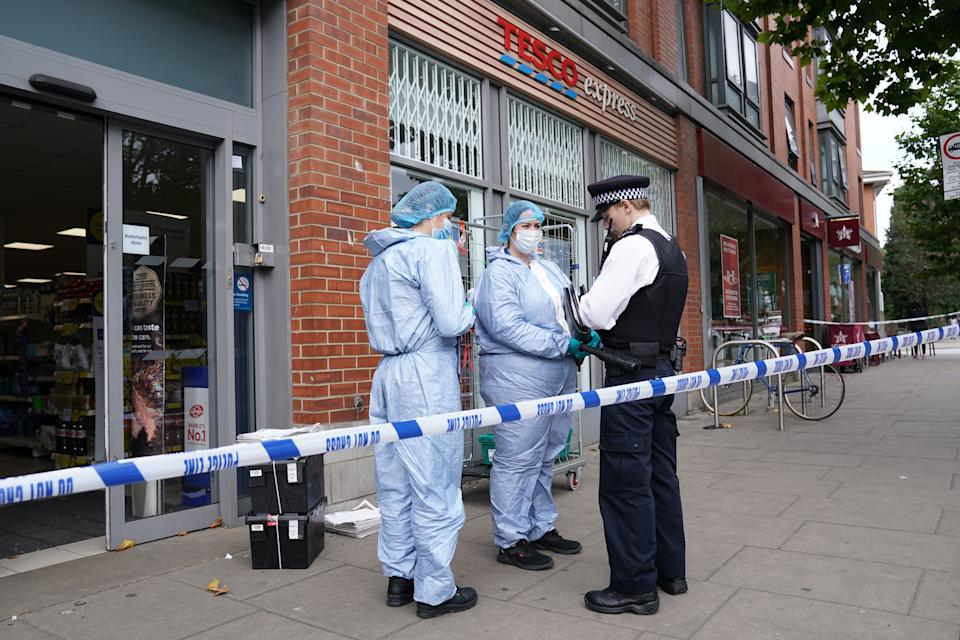 Police officers in forensic suits speak to a colleague outside Tesco Express on Fulham Palace Road, west London.