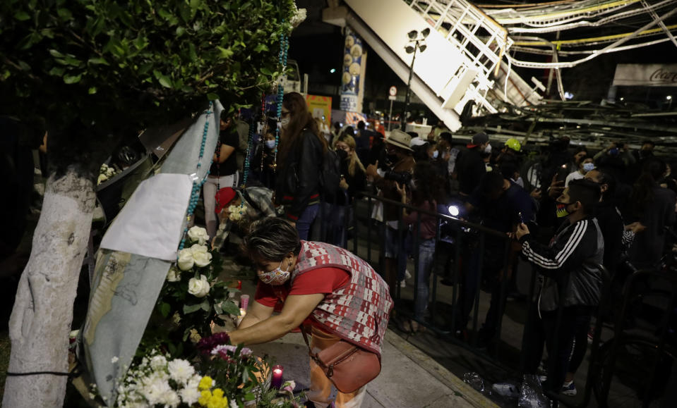 A woman places flowers at a makeshift altar during a protest demanding justice for the people who died in Monday's subway collapse, at the site of the wreckage in Mexico City's south side, Friday, May 7, 2021. An elevated section of Line 12 collapsed late Monday killing at least 25 people and injuring more than 70, city officials said. (AP Photo/Eduardo Verdugo)