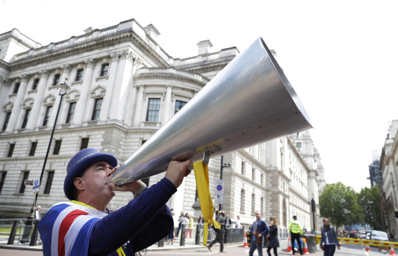 Anti Brexit campaigner Steve Bray shouts through his megaphone outside Conservative leadership contender press conferences, in London, Tuesday, June 11, 2019. (AP Photo/Kirsty Wigglesworth)