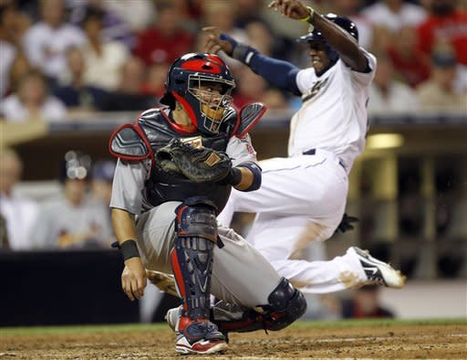 San Diego Padres' Cameron Maybin, right, scores on a slide home to beat the throw to St. Louis Cardinals catcher Yadier Molina, left, from Cardinals first baseman Allen Craig (not pictured) on a fielder's choice during the eighth inning of their baseball game in San Diego, Calif., Monday, Sept. 10, 2012. (AP Photo/Alex Gallardo)