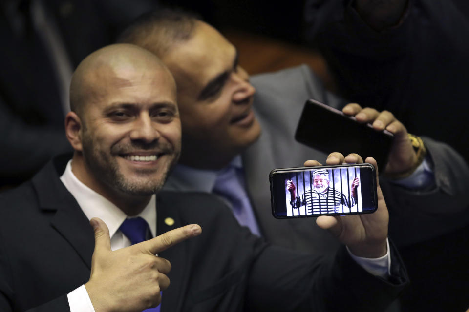 Deputy Daniel Silveira, who was elected to his first term representing the Social Liberal Party from where President Jair Bolsonaro mounted his campaign, points to his phone showing an image spoofing the jailed President former President Luiz Inacio Lula da Silva, during a swearing-in ceremony in the Chamber of Deputies, in Brasilia, Brazil, Friday, Feb. 1, 2019. (AP Photo/Eraldo Peres)