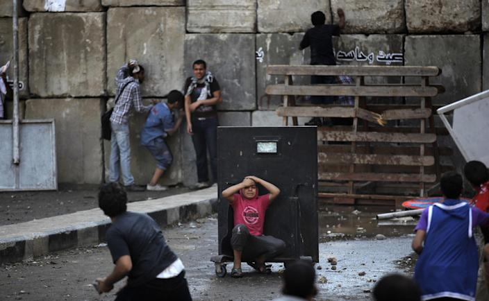An injured Egyptian youth protester takes cover behind a metal barrier during clashes with riot police, unseen, behind cement blocks that are used to close the street leading to the U.S. embassy in Cairo, Egypt, Friday, Sept. 14, 2012, as part of widespread anger across the Muslim world about a film ridiculing Islam's Prophet Muhammad. (AP Photo/Nasser Nasser)
