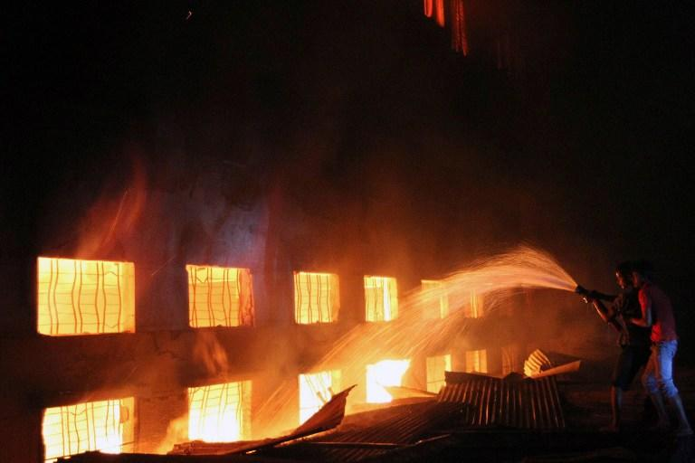 This picture taken on 24 November, 2012 shows Bangladeshi people and firefighters trying to extinguish a fire in a garment factory in Savar, 30 kilometres north of Dhaka. The death toll from a fire at a Bangladeshi factory soared to at least 121 as rescue workers recovered 112 bodies on November 25, the national fire chief told AFP. AFP PHOTO / PALASH KHAN