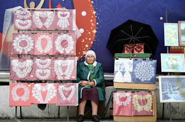 A elderly woman sells lacy collars in the streets of Yekaterinburg hours before the Russia 2018 World Cup Group C football match between France and Peru (AFP Photo/FRANCK FIFE)