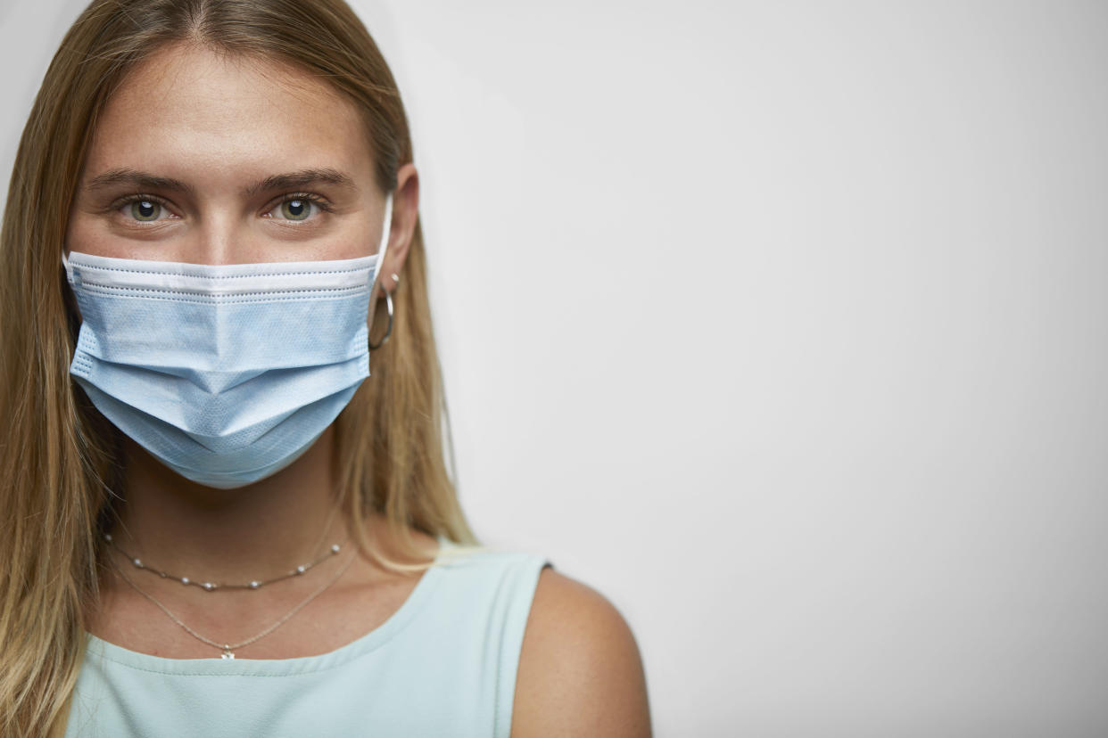 Closeup portrait of a young woman with face mask on the studio against white background.