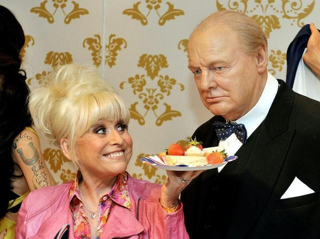 Barbara Windsor offers the wax figure of Sir Winston Churchill some lunch at Madame Tussauds