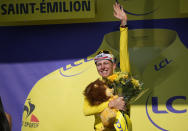 Slovenia's Tadej Pogacar, wearing the overall leader's yellow jersey, celebrates on the podium after the twentieth stage of the Tour de France cycling race, an individual time-trial over 30.8 kilometers (19.1 miles) with start in Libourne and finish in Saint-Emilion, France, Saturday, July 17, 2021. (AP Photo/Christophe Ena)