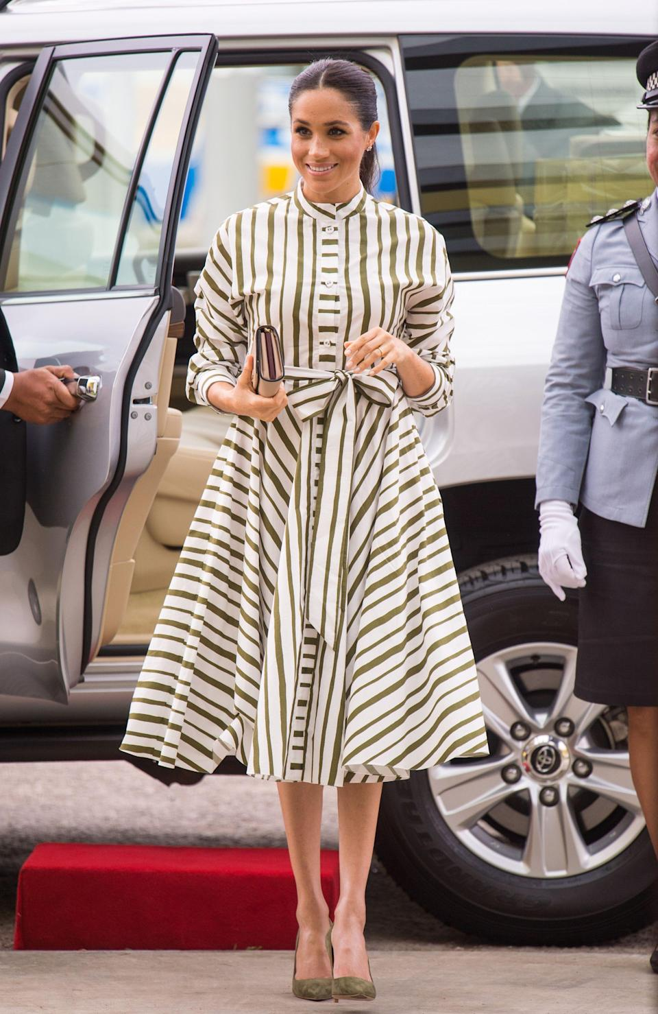 """<p>Meghan Markle opted for a cotton green and white striped dress from <a href=""""https://www.modaoperandi.com/martin-grant-ss19/striped-cotton-dress?country=GB&gclid=CjwKCAjw9sreBRBAEiwARroYm9a-bx3oFjpg4AuR7dCDnwql7gqBydml5Q6ng9Ylowj6LDGSmFCSSBoCGm4QAvD_BwE&gclsrc=aw.ds"""" rel=""""nofollow noopener"""" target=""""_blank"""" data-ylk=""""slk:Martin Grant's SS19 resort collection"""" class=""""link rapid-noclick-resp"""">Martin Grant's SS19 resort collection</a>.</p><p>She teamed the look with suede green heels and a <a href=""""https://www.net-a-porter.com/gb/en/Shop/Designers/Prada/Bags?keywords=Prada&pn=1&npp=60&image_view=product&dScroll=0"""" rel=""""nofollow noopener"""" target=""""_blank"""" data-ylk=""""slk:Prada"""" class=""""link rapid-noclick-resp"""">Prada</a> nude-coloured clutch bag.</p>"""