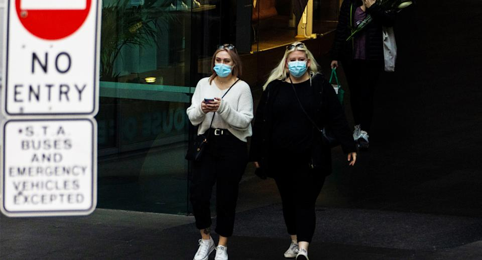Two women wear face masks in Sydney during the coronavirus pandemic.