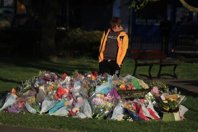 Patrick James, the son of PCSO Julia James, looks at floral tributes left near her family home in Snowdown, near Aylesham, Kent