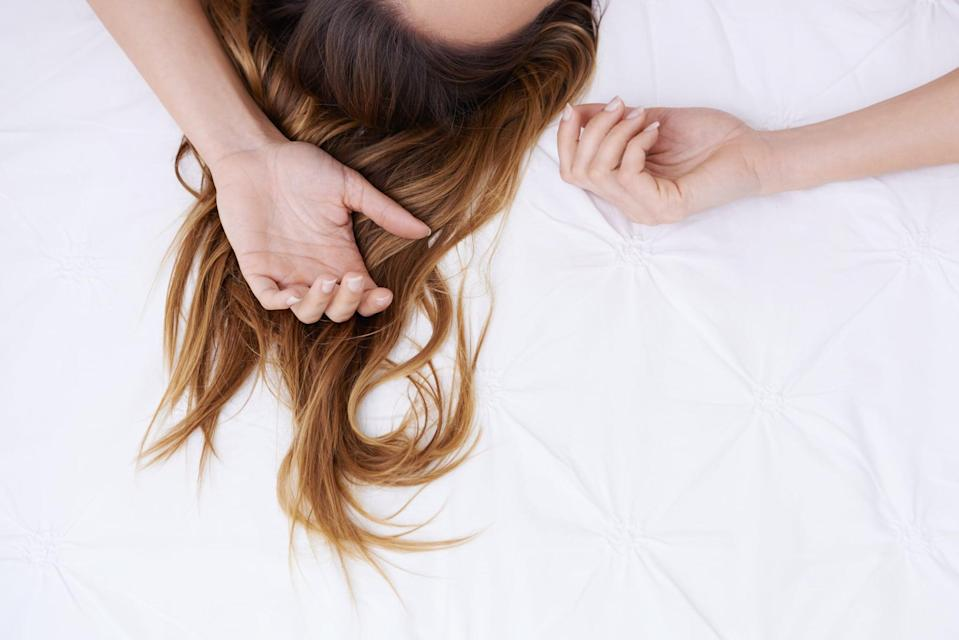 Cropped image of a woman's hair lying sprawled on a bed