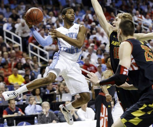 North Carolina's Dexter Strickland, left, passes the ball past Maryland's Alex Len, right, and Jake Layman, rear, during the first half of an NCAA college basketball game in the semifinals of the Atlantic Coast Conference tournament in Greensboro, N.C., Saturday, March 16, 2013. (AP Photo/Gerry Broome)
