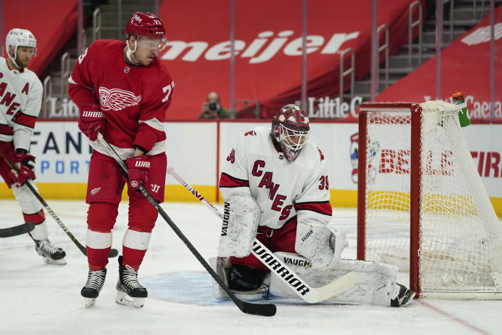 Carolina Hurricanes goaltender Alex Nedeljkovic (39) stops a shot as Detroit Red Wings left wing Adam Erne (73) watches for a rebound in the second period of an NHL hockey game Sunday, March 14, 2021, in Detroit. (AP Photo/Paul Sancya)