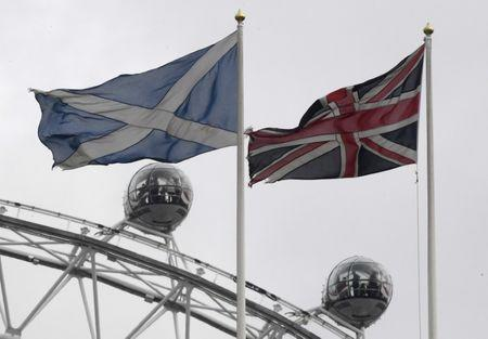 The British Union Flag and a Scottish Saltire flag fly above the Scottish Office in Whitehall, with the London Eye wheel seen behind, in London, Britain