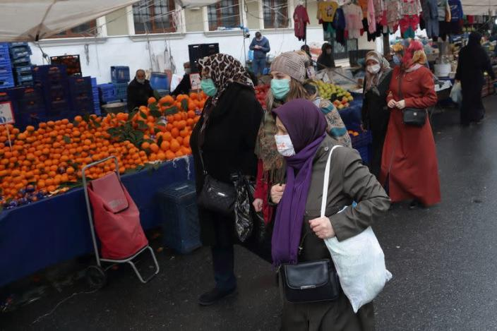 People shop at a local market in Fatih district in Istanbul