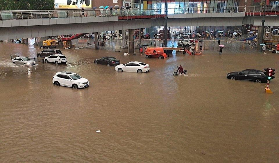 People wade through floodwaters along a street in Zhengzhou in central Henan province. Photo: AFP