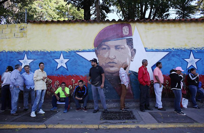 Residents wait in line to enter a polling station to vote in front of a wall painting depicting late president Hugo Chavez during municipal elections in Caracas, Venezuela, Sunday, Dec. 8, 2013. Venezuelans head to the polls to elect mayors and city councilors at a moment when the country's economic troubles have deepened, with inflation touching a two-decade high of 54 percent, and shortages of everything from toilet paper to milk spreading while the black market value of the currency plunges. (AP Photo/Ariana Cubillos)