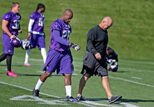 Minnesota Vikings' Adrian Peterson, second from right, makes his way onto an NFL football practice field at Winter Park in Eden Prairie, Minn., Friday, Oct. 11, 2013. Peterson said he is certain he will play Sunday despite a serious personal matter that caused him to miss practice earlier this week. (AP Photo/The Star Tribune, Elizabeth Flores)