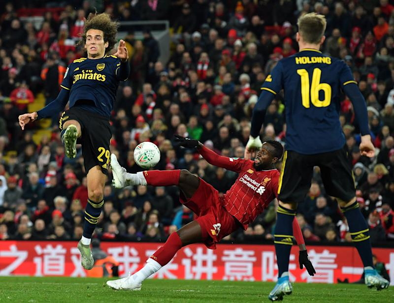 Liverpool's Belgium striker Divock Origi (C) scores his team's fifth goal during the English League Cup fourth round football match between Liverpool and Arsenal at Anfield in Liverpool, north west England on October 30, 2019. (Photo by Paul ELLIS / AFP) / RESTRICTED TO EDITORIAL USE. No use with unauthorized audio, video, data, fixture lists, club/league logos or 'live' services. Online in-match use limited to 75 images, no video emulation. No use in betting, games or single club/league/player publications. / (Photo by PAUL ELLIS/AFP via Getty Images)