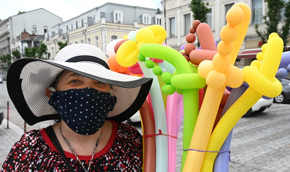 A street vendor wearing a face mask sells inflatable balloons in central Tbilisi on June 3, 2020, as Georgia lifted most of the restrictions on economic activity that were imposed as part of measures to contain the coronavirus spread. - Industrial production and trade are allowed to resume, with the exception of large shopping malls and clothing retailers. (Photo by Vano Shlamov / AFP) (Photo by VANO SHLAMOV/AFP via Getty Images)