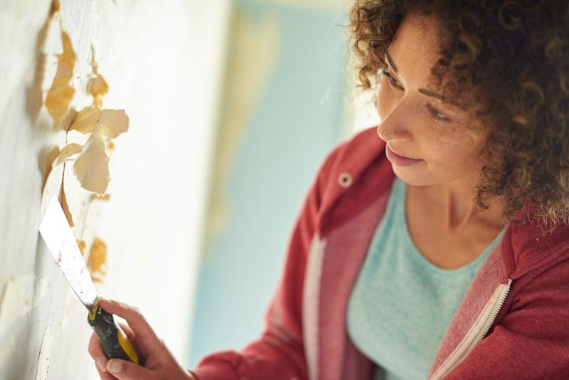 woman with putty knife removing wallpaper