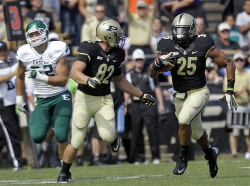 Purdue running back Brandon Cottom (25) heads for the end zone on an 87-yard touchdown past teammate tight end Crosby Wright, center, and Eastern Michigan defensive lineman Pat O'Connor during the first half of an NCAA college football game in West Lafayette, Ind., Saturday, Sept. 15, 2012. (AP Photo/Michael Conroy)