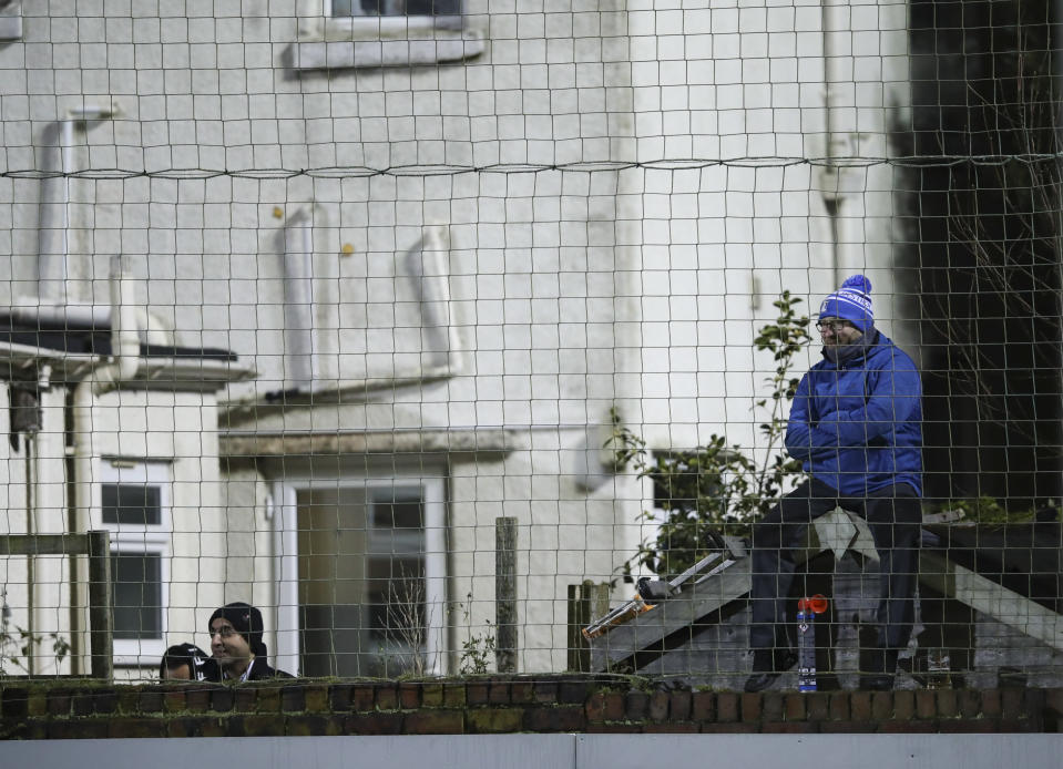 A fan seated on a garden shed watches the English FA Cup third round soccer match between Marine and Tottenham Hotspur at Rossett Park stadium in Crosby, Liverpool, Sunday, Jan. 10, 2021. (Clive Brunskill/Pool via AP)