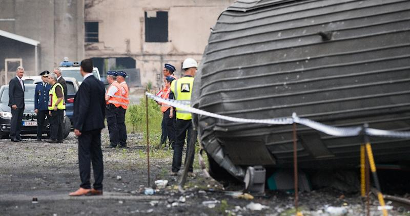 King Philippe of Belgium (L) looks at the scene of a train collision between a freight train and a passengers train on the line between Liege and Namur, in Saint-Georges-sur-Meuse on June 6, 2016 (AFP Photo/Benoit Doppange)
