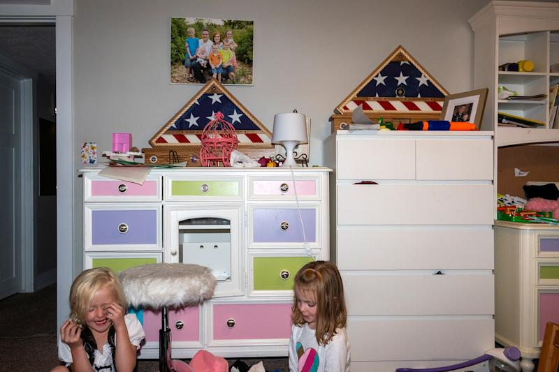 Ellie plays with cousin Vivian Pack in her bedroom. Resting on the dressers are two framed flags presented to each member of the family by the U.S. military.   Peter van Agtmael—Magnum Photos for TIME