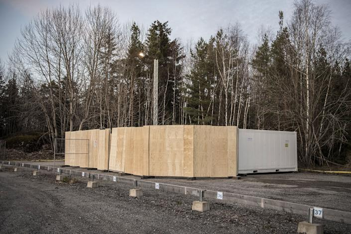 "Refrigeration containers to be used on standby as makeshift morgues to store people who have died from COVID-19 set up behind Karolinska University Hospital in Huddinge, Sweden on March 26, 2020.<span class=""copyright"">IBL/Shutterstock</span>"
