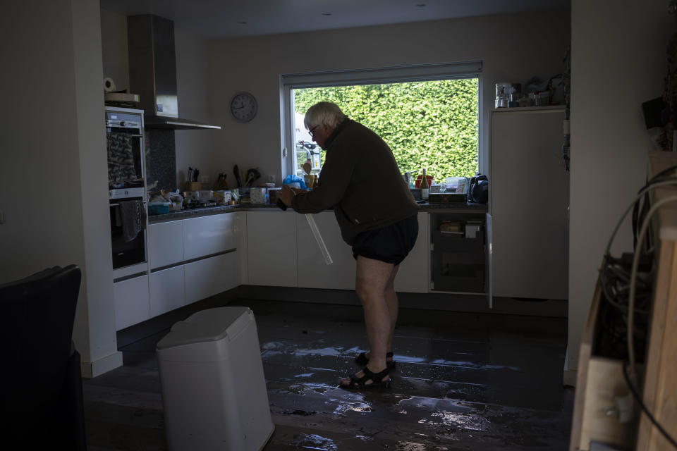IJmert Kant assesses the damage in his home in the town of Brommelen, Netherlands, Saturday, July 17, 2021. In the southern Dutch province of Limburg, which also has been hit hard by flooding, troops piled sandbags to strengthen a 1.1-kilometer (0.7 mile) stretch of dike along the Maas River, and police helped evacuate low-lying neighborhoods. (AP Photo/Bram Janssen)