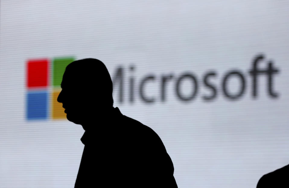 FILE - In this Nov. 7, 2017, file photo, a man is silhouetted as he walks in front of Microsoft logo at an event in New Delhi, India. Microsoft says it's uncovered new Russian hacking attempts targeting U.S. political groups ahead of the midterm elections. The company said Tuesday, Aug. 21, 2018, that a hacking group tied to the Russian government created fake internet domains that appeared to spoof two conservative organizations: the Hudson Institute and the International Republican Institute. (AP Photo/Altaf Qadri, File)
